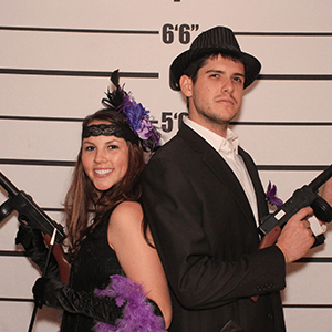 Toledo Murder Mystery party guests pose for mugshots